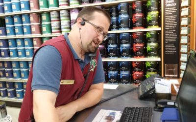Coles Employee at Register on Phone with Customer