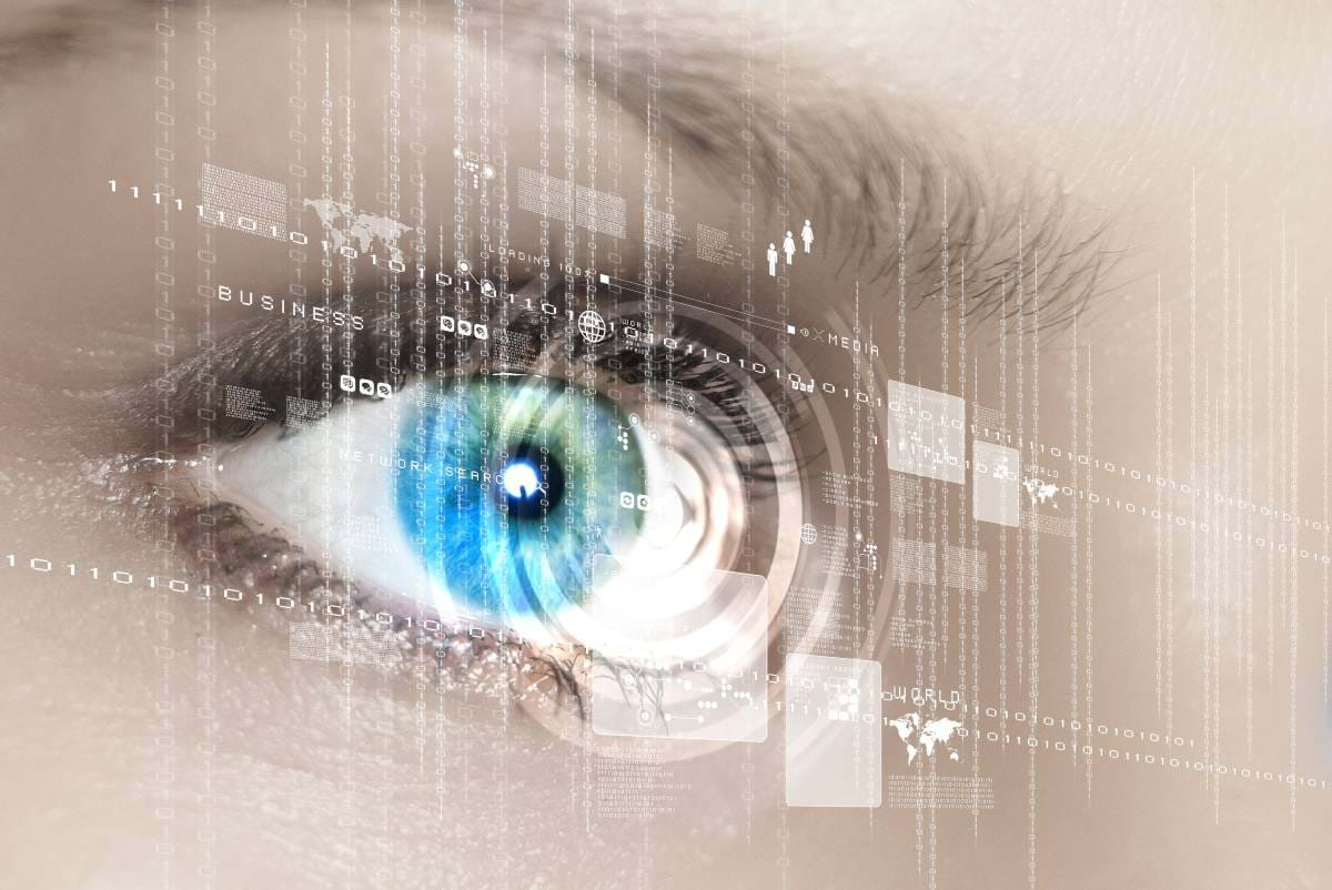 A close up of a woman's eye with a graphical overlay of binary and continents
