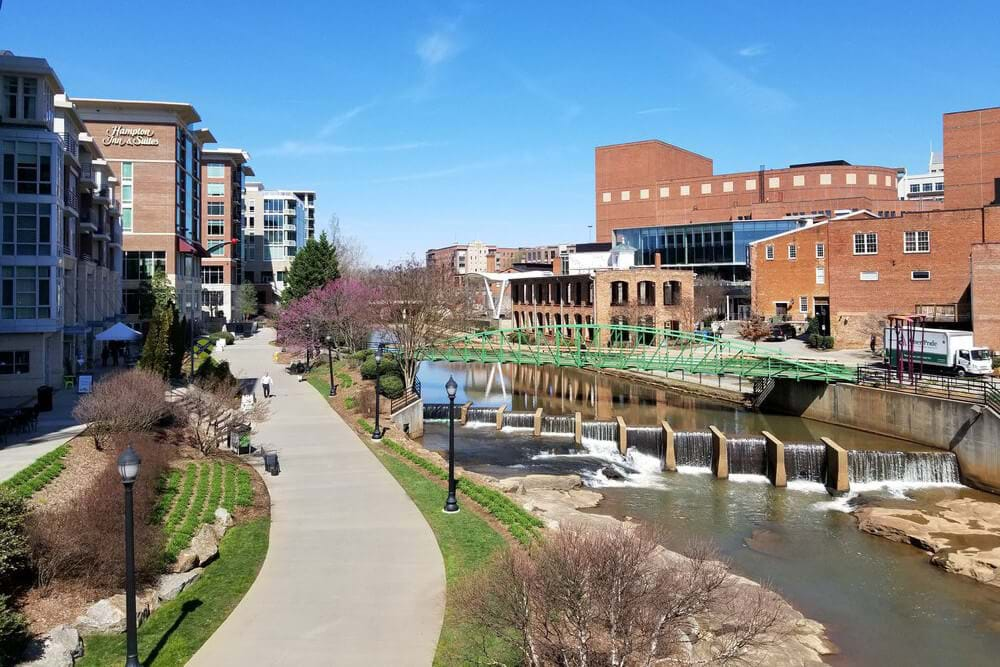 Downtown Greenville, NC, sidewalk along river with green bridge spanning it