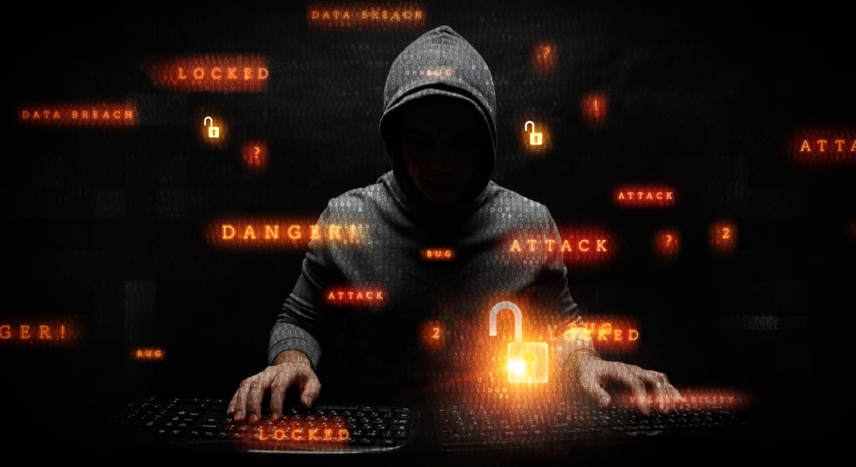 A hooded figure typing on two keyboards, with orangish-red text floating around him indicating he is committing cybercrimes