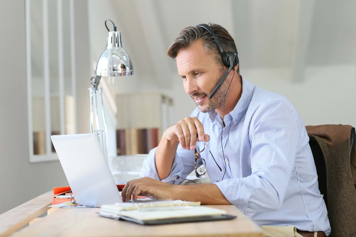 A man wearing a headset working from home on his laptop while taking notes