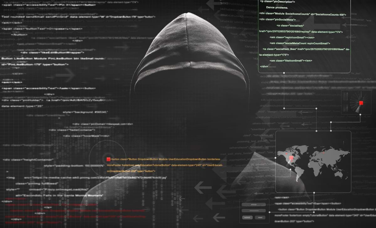 A man with his face concealed by a black pulled up hoodie, looking at all the data displayed in front of him.