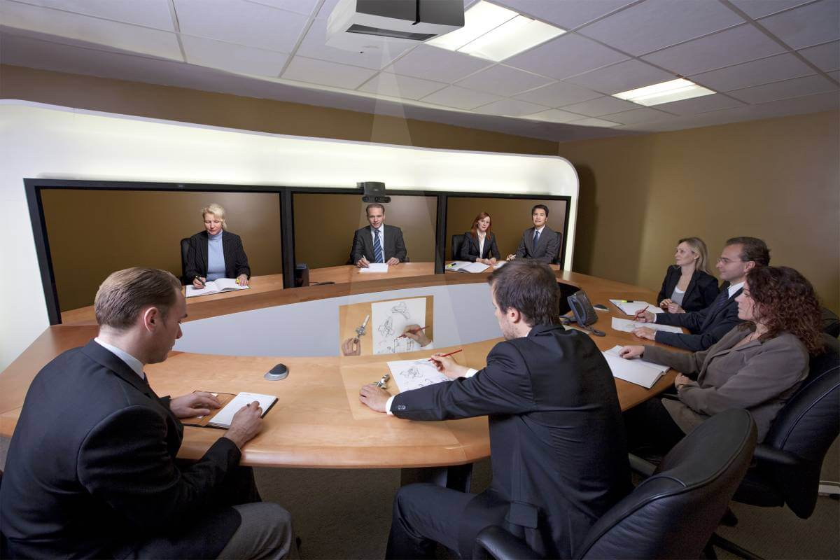Business people sitting around a table with screens in front of them on a video conference