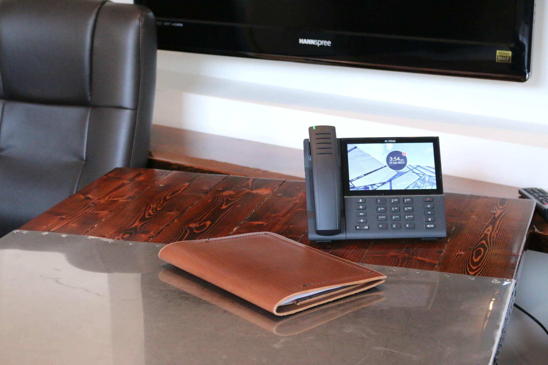 Front View of Mitel 6873 SIP Phone on Wooden Desk with Laether Folder